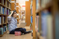 Young Asian university student in library. Young Asian man university student thinking about his project homework and using laptop computer in library, education Stock Photo