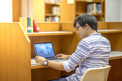 Young Asian university student in library. Young Asian man university student thinking about his project homework and using laptop computer in library, education stock images