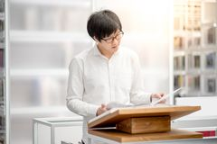 Young Asian university student reading book in library Royalty Free Stock Images