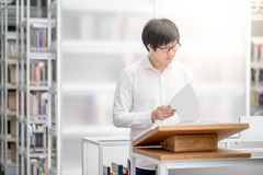 Young Asian university student reading book in library Stock Images