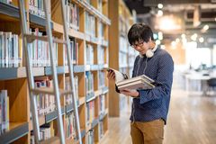 Young Asian university student reading book in library. Young Asian man university student reading book in library, education research and self learning in Stock Photos