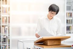 Young Asian university student reading book in library. Young Asian man university student reading recommended book on podium in library, education research and royalty free stock photo