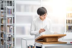 Young Asian university student reading book in library. Young Asian man university student reading recommended book on podium in library, education research and Stock Photography