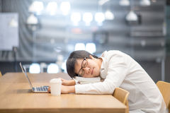 Young Asian university student take a nap in library. Young Asian university student take a nap on book stack during doing homework in library, college lifestyle royalty free stock images