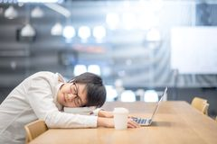 Young Asian university student take a nap in library. Young Asian man university student take a nap on book stack during doing homework in library, college Royalty Free Stock Photos