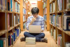 Young Asian university student using laptop in library. Young Asian man university student thinking about his project homework and using laptop computer in Stock Photography