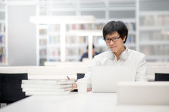 Young Asian university student working in library Royalty Free Stock Photo
