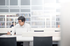 Young Asian university student working in library Stock Photos