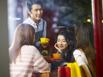 Young asian waiter serving coffee to customers. Young asian waiter serving female customers in coffee shop, shot through window glass Royalty Free Stock Images
