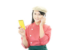 Young Asian waitress with smartphone Royalty Free Stock Image