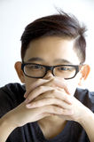 Young asian wear specs looking at you. In serious face Royalty Free Stock Photography