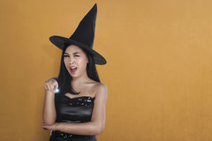 Young asian witch woman in hat using magic spell Stock Images