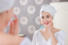 Young asian woman applying foundation or moisturizer on her face stock photography
