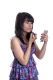 Young asian woman applying lip gloss. Royalty Free Stock Photography