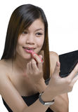 Young Asian woman applying makeup Royalty Free Stock Photography