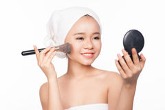 Young asian woman applying powder with a cosmetic brush on her face. Looking to the mirror makeup. Isolated on white background. Young asian woman applying Stock Images