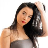 Stunning young woman runs her hand through her dark long hair. Young Asian woman in bare shoulders runs her hand through her long dark tresses Royalty Free Stock Photography
