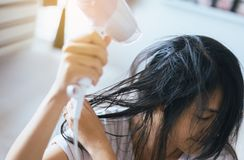 Young asian woman after bath hairbrushing her hair with comb,Female drying her long hair with dryer. Close-up stock photography