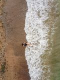 Young asian woman on the beach on the sand near the waves. Young asian woman on the beach on the sand near the waves, Aerial top view royalty free stock photography