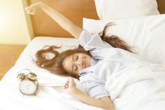 Young Asian woman in bed trying to wake up with alarm clock royalty free stock photo