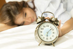 Young Asian woman in bed trying to wake up with alarm clock Royalty Free Stock Images