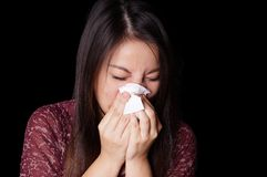Young asian woman blowing nose. Young asian woman blowing her nose with paper tissue Stock Photos