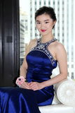 Young Asian Woman in Blue Gown. Young Asian woman models a blue gown seated in an urban setting Royalty Free Stock Photos
