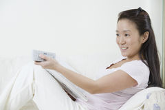 Young Asian woman with book and remote control Stock Photos