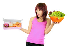 Young asian woman with a box of donut and a bowl of veg Stock Photos