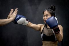 Young Asian woman boxer punching to her trainer Royalty Free Stock Images
