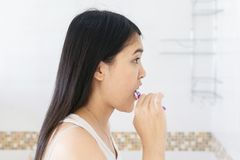 Young asian woman brush the teeth in bathroom after wake up in morning Royalty Free Stock Photos