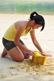 Young Asian Woman Building Sandcastle. Royalty Free Stock Images