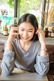Young asian woman at cafe drinking coffee and talking on the mob. Ile phone with laptop stock photography