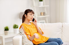Young asian woman calling on smartphone at home. People, technology, communication and problem concept - young asian woman calling on smartphone at home Stock Images