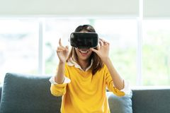 cf2cfe072752 Young asian woman in casual yellow shirt wearing VR glasses watching video  or enjoy playing videogame