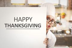Young asian woman chef holding white banner with Happy Thanksgiv Stock Photos