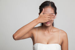 Young Asian woman close her eyes with hand. Royalty Free Stock Photography