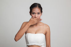 Young Asian woman close her mouth with hand. Royalty Free Stock Photos