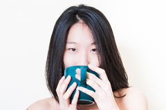 Young asian woman closeup drinking from blue-green cup Stock Photography