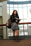 Young asian woman in college. Young asian woman holding a copybook and with college buildings as background Stock Photos