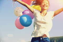 Young asian woman with colored balloons Stock Images