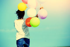 Young asian woman with colored balloons Stock Photography