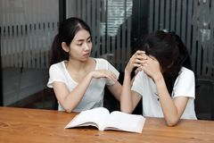 Young Asian woman comforting her depressed friend in living room royalty free stock photos