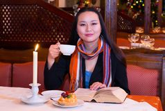 Coffee in the evening. Young Asian woman with a cup sits at a table looking at camera. A burning candle, cake and a book are on the table. Warm evening indoors Stock Photos