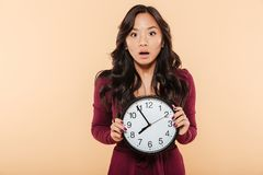 Young asian woman with curly long hair holding clock showing nearly 8 being late or missing something over peach background stock image