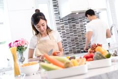 Young asian woman cutting slice vegetables making salad heathy food. Young asian women cutting slice vegetables making salad healthy food with fruits and men Stock Image