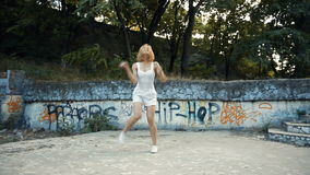 Young Asian woman dancing modern choreography in city park, outside. City ruins and graffiti Variety stock footage