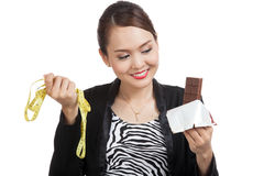Young Asian woman on diet with chocolate bar and measuring tape Royalty Free Stock Photos