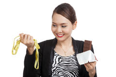 Young Asian woman on diet with chocolate bar and measuring tape Royalty Free Stock Images