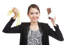 Young Asian woman on diet with chocolate bar and measuring tape Royalty Free Stock Image